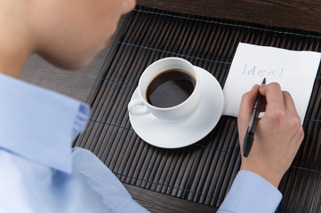Hands of businesswoman writing on paper napkin on coffee table.
