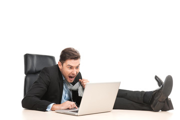 Angry businessman working at his laptop computer.