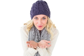 Pretty blonde in winter fashion blowing over hands