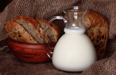 jug with milk and whole grain bread