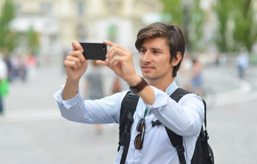Young handsome man photographing with mobile smart phone walking
