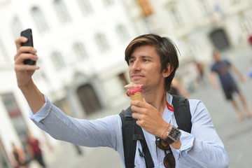 Selfie of handsome young man eating ice cream on the street