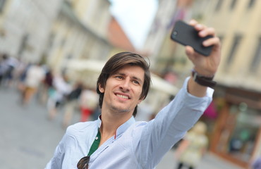 Young fashionable hipster Hispanic man  taking a selfie