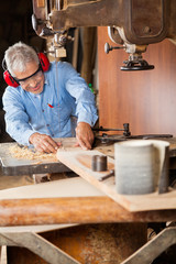 Carpenter Using Bandsaw To Cut Wood