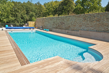 Summer outdoor swimming pool with green trees.