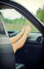 Woman's legs lying on the car dashboard.
