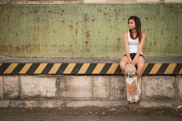 Beautiful skater girl in summer city