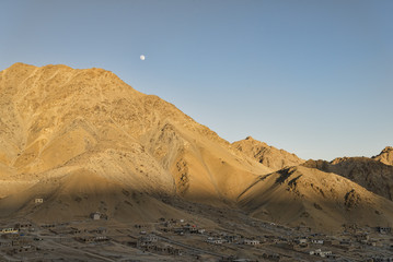 Ancient village in mountains under the moon