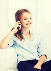smiling girl with smartphone at home