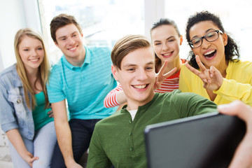 smiling students making selfie with tablet pc