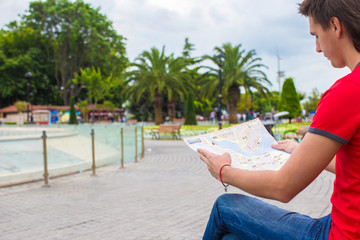 Young caucasian traveling man reading a map
