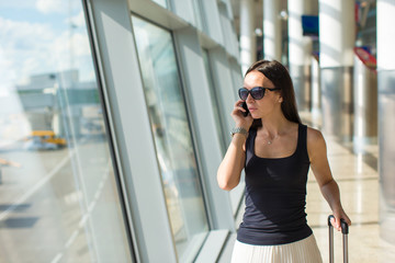 Young businesswoman talking on the phone while waiting for her