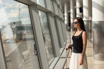 Young woman with hand luggage at the international airport
