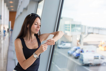 Young woman writing message on phone while waiting for flight