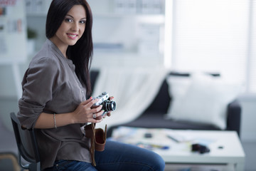 Woman is a proffessional photographer with camera in office