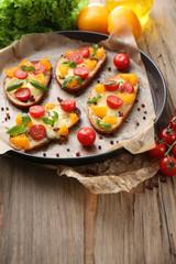 Photo sur Aluminium Singapoure Tasty bruschetta with tomatoes on pan, on old wooden table