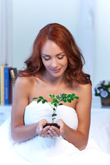 Woman holding little plant in her hands.