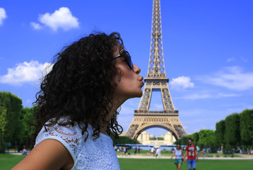 Fototapete - Beautiful girl kisses Eiffel tower, Paris, France