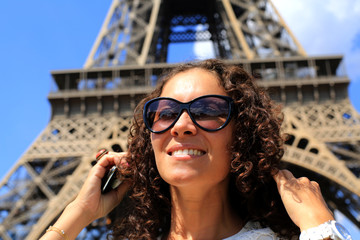 Fototapete - Beautiful young woman on the Eiffel tower in Paris