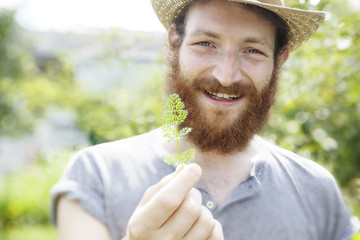 young beauty bearded farmer man holding a little cute leaf