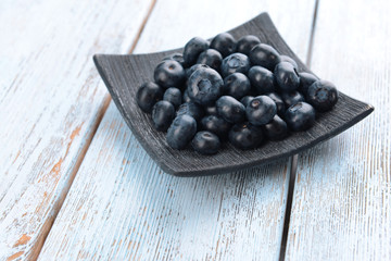 Delicious blueberries on plate on table close-up
