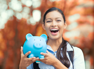Happy, laughing business woman holding piggy bank