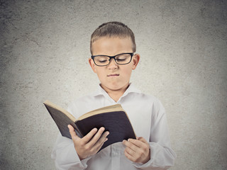 Unhappy Boy Reading Book, isolated on grey wall background