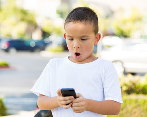 Surprised boy looking at his smart phone, outdoor background
