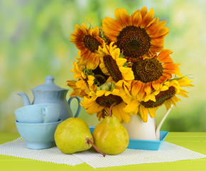 Beautiful sunflowers in pitcher with cups and pears