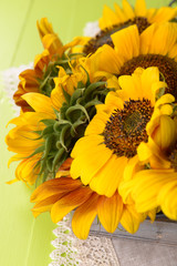 Beautiful sunflowers in pitcher on napkin on table close up
