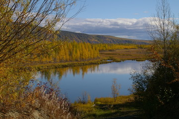 Autumn colors surround a lake and gray clouds above