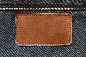 Leather tag on jeans background