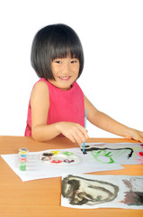 Asian little girl paints pictures with color brush