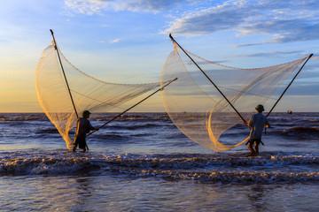 Fishermen fishing in the sea at sunrise