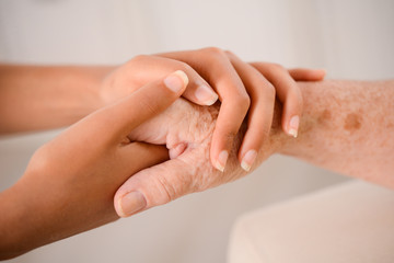 young woman's hands holding tenderly hand of elderly person