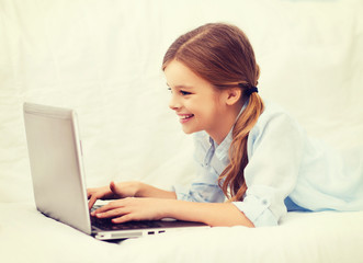 smiling girl with laptop computer at home