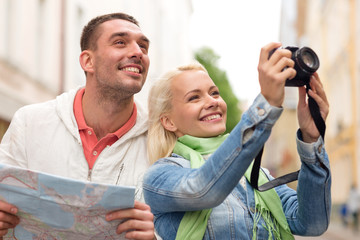 smiling couple with map and photocamera in city
