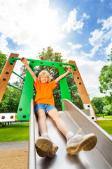Boy sliding on metallic chute with hands up