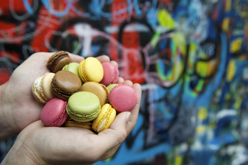 Hands Holding Pile of Colorful Macaroon Cookies