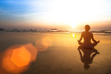 Silhouette of a woman meditating on the beach at sunset.