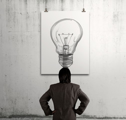 businessman looking at light bulb in art frame on the wall as co
