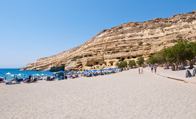 Holidaymakers on Matala beach with the caves on Crete, Greece.
