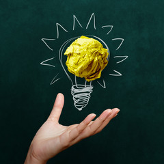 hand holding crumpled paper with Light bulb on blackboard backgr