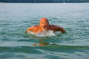 Swimmer, Senior man swimming butterfly strokes.