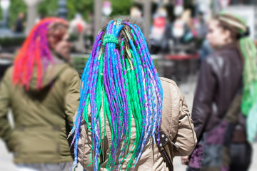 girls with colorful dreadlocks walking in the street