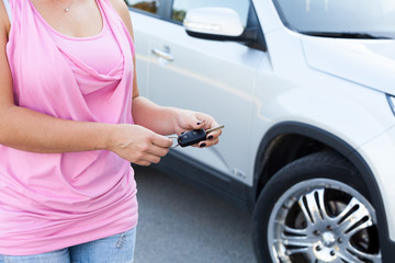Unrecognizable woman with ignition key stands near own vehicle