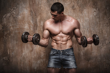 Naked muscular man working out with dumbbells on wall background