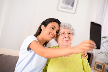 two generation womans making a funny selfie together at home