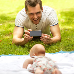 Father with baby In Park  taking selfie by mobile phone