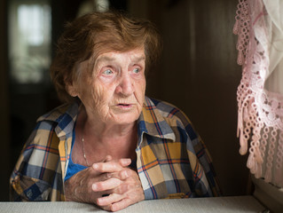 Close-up shot of elderly woman sitting at table in his house.